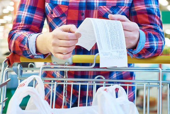 woman looking at grocery bill